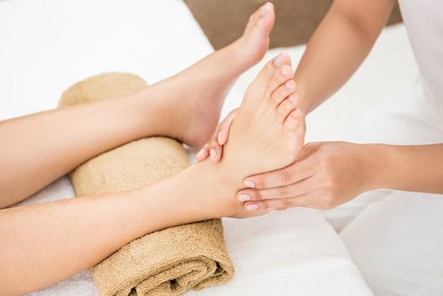 Terapista che dà il massaggio di rilassamento tailandese di riflessologia plantare ad una donna in stazione termale