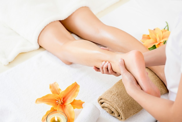 Terapista che dà il trattamento tailandese di massaggio della gamba dell'olio ad una donna in stazione termale