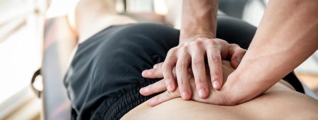 Terapista che dà massaggio della parte posteriore della parte inferiore al paziente maschio dell'atleta