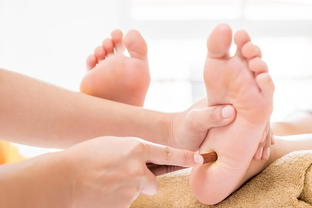 Terapista che dà riflessologia che si rilassa massaggio tailandese tradizionale del piede della stazione termale con il bastone
