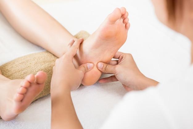 Terapista che dà rilassante riflessologia plantare massaggio tailandese ai piedi a una donna nella spa