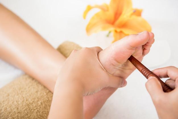 Terapista che dà rilassante riflessologia plantare thai massaggio ai piedi con un bastone per una donna nella spa