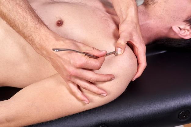 Terapista che fa la fibrolisi diacutanea, dei ganci che curano il trattamento sulla schiena dell'uomo.