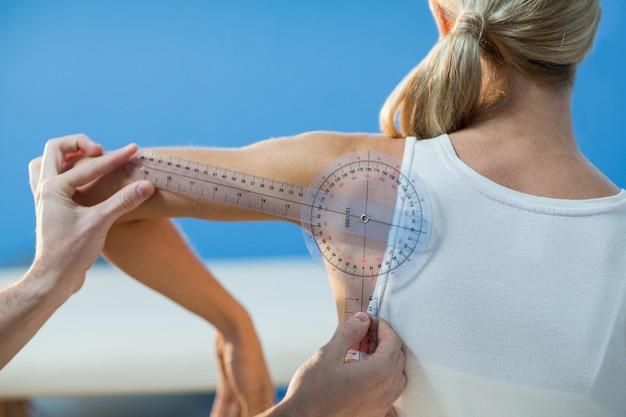 Terapista maschio che misura spalla paziente femminile con goniometro