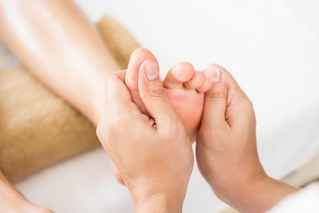 Terapista professionista che dà riflessologia massaggio tailandese del piede ad una donna nella spa
