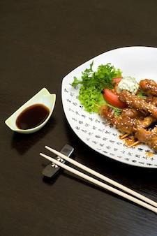 Teriyaki di pollo sul piatto bianco, sacco di copyspace