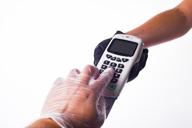 Terminale di pagamento. mani con i guanti. la mano del venditore in un guanto. la mano dell'acquirente in un guanto. concetto di acquisto sicuro
