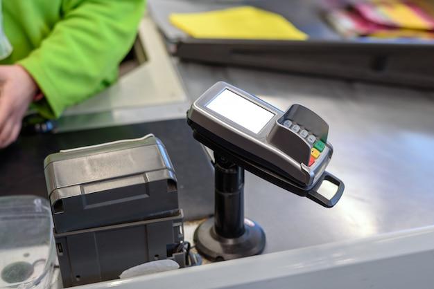 Terminale di pagamento per carte di plastica presso il negozio con spazio per il layout, mock up