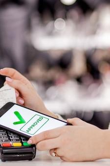 Terminale pos, macchina di pagamento con telefono cellulare sullo sfondo del negozio. pagamento senza contatto con tecnologia nfc