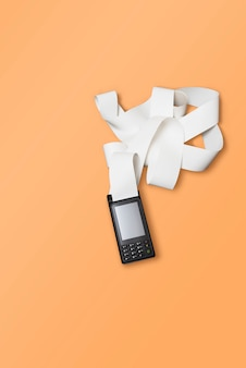 Terminale pos per carte di credito wireless per pagamenti e nastro di cassa a rotolo lungo su un arancio.