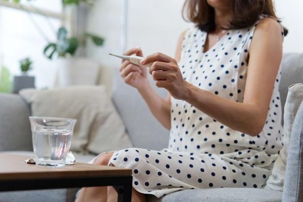 Termometro asiatico della lettura della donna incinta prima di prendere la medicina.
