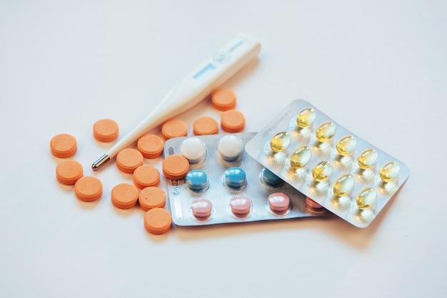 Termometro con temperatura elevata e molte pillole su sfondo chiaro