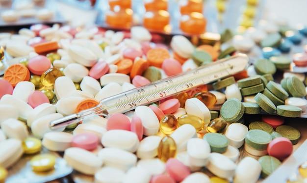 Termometro e diversi tipi di pillole colorate. concetto di salute o droghe mediche