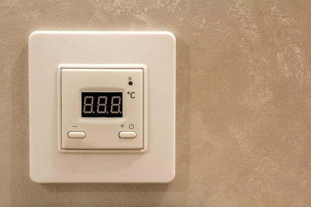 Termostato digitale programmabile elettronico bianco sul fondo leggero dello spazio della copia della parete. controllo del clima, temperatura domestica confortevole, concetto di risparmio energetico.