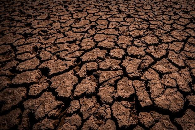 Terra marrone, terriccio argilloso ricoperto da profonde crepe nell'oscurità