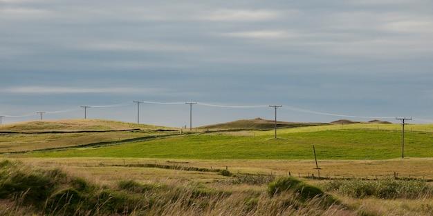 Terreno agricolo remoto con telefono posato e recinto di filo