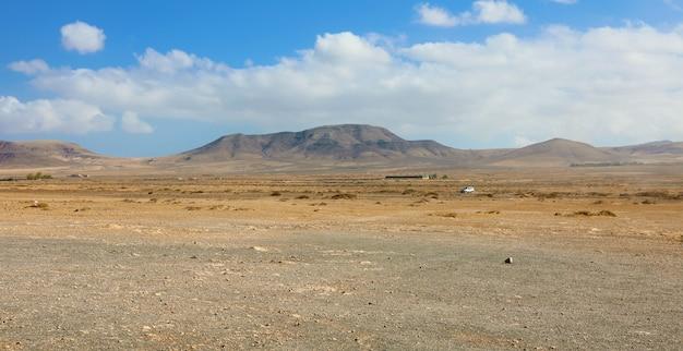 Terreno asciutto sotto nuvole bianche e cielo blu con montagne sull'isola di fuerteventura