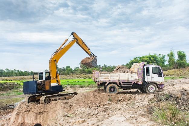 Terreno di caricamento a macchina giallo dell'escavatore in un autocarro con cassone ribaltabile al cantiere