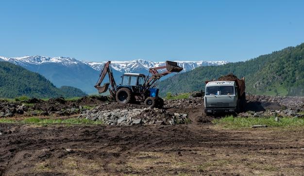 Terreno di caricamento dell'escavatore industriale dalla sabbionaia in un autocarro con cassone ribaltabile