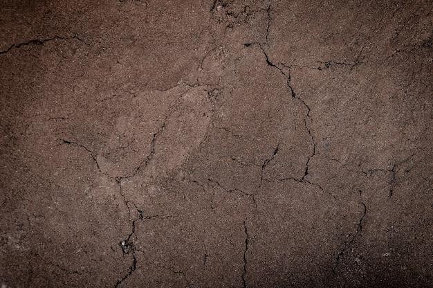 Terreno incrinato e arido, fondo strutturato del terreno asciutto, forma di strati di terreno, il suo colore e le sue trame, strati di terra per lo sfondo