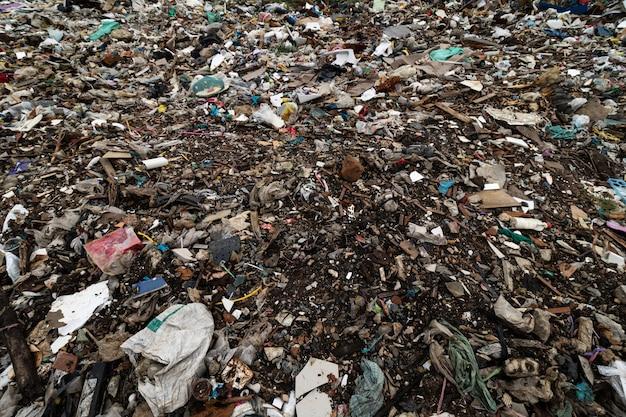 Terreno sporco e pieno di detriti causati dallo scarico da fabbriche o industrie e case.