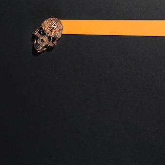 Teschio di gioielli con fulmine posato su una striscia di carta arancione