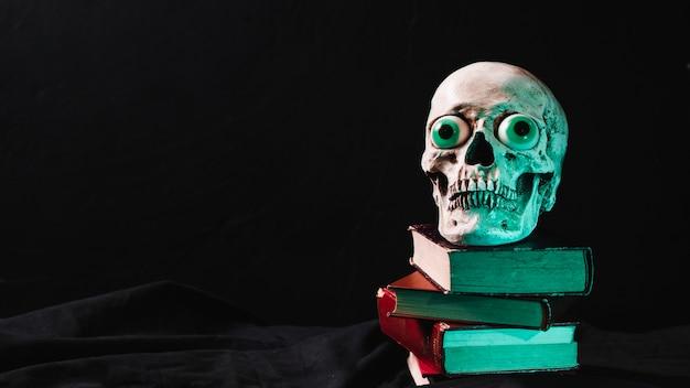 Teschio spettrale con occhi di fantasia su una pila di libri