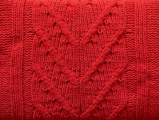Tessitura a maglia di lana rossa tessuto a maglia con motivo a cavo come sfondo.