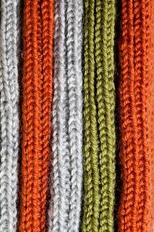 Tessitura a maglia in lana arancione, verde e grigia.