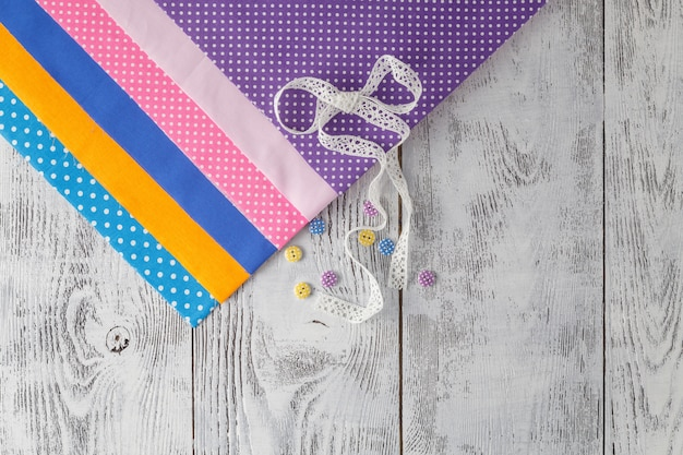 Tessuti di cotone per cucire, pizzi e accessori per ricamo su fondo di legno. impostare per la vista dall'alto del ricamo