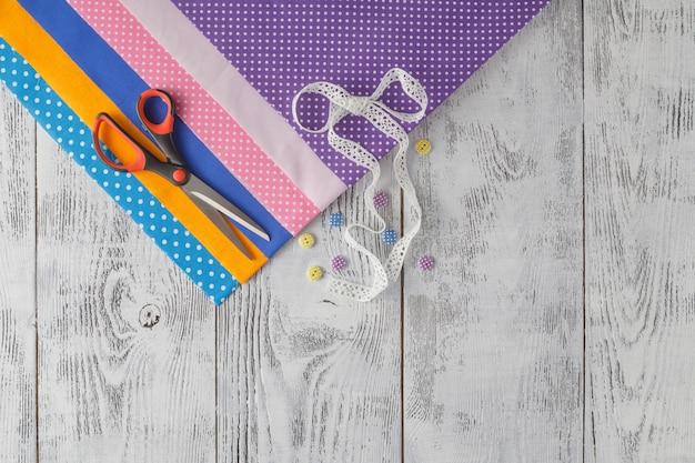Tessuti di cotone per cucire, pizzi e accessori per ricamo su fondo di legno.