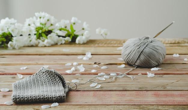 Tessuto a maglia su fondo in legno con fiori bianchi