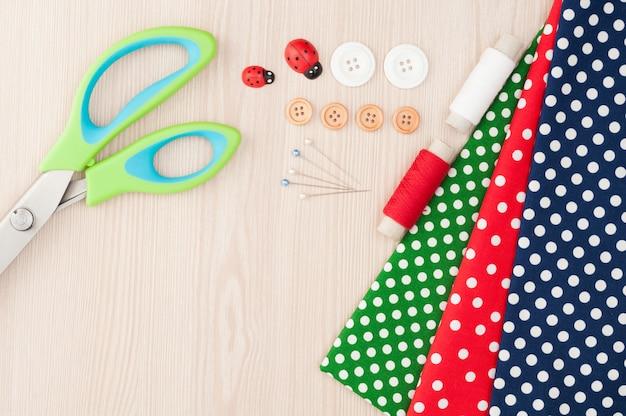 Tessuto a pois per cucito e accessori per ricamo. rocchetto di filo, forbici, bottoni, forniture per cucire. impostare per la vista dall'alto del ricamo