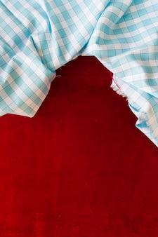 Tessuto a quadretti blu e bianco su tessuto bordeaux