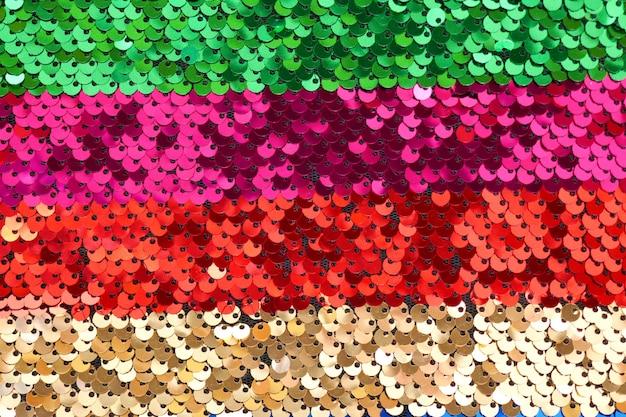 Tessuto a righe con paillettes. squame di scale con il primo piano di paillettes. striscia multicolore in paillettes.