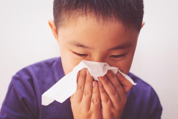 Tessuto asiatico di malattia di influenza fredda del ragazzo che soffia naso che cola