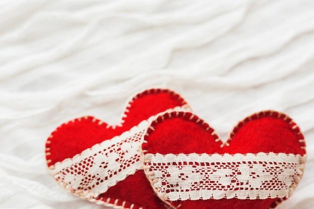Tessuto bianco con ruche. due cuori in feltro con lacci, simbolo dell'amore. buono per le carte di san valentino. posto per il testo.