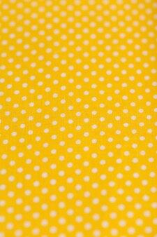 Tessuto di cotone giallo con pois bianchi