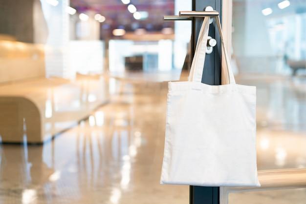 Tessuto di tela tote bag, appeso su una maniglia della porta nella sala riunioni in ufficio con sfocatura dello sfondo.