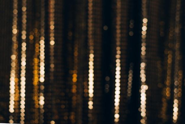 Tessuto dorato lucido con paillettes, fondo astratto blured.