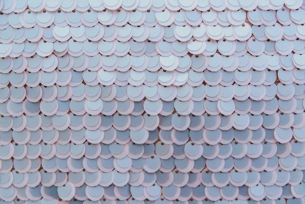 Tessuto lucido beige con paillettes, sfondo astratto.