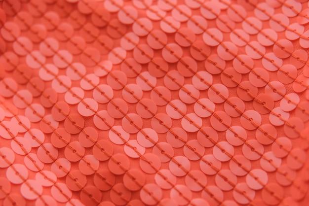 Tessuto lucido corallo con paillettes, sfondo astratto.