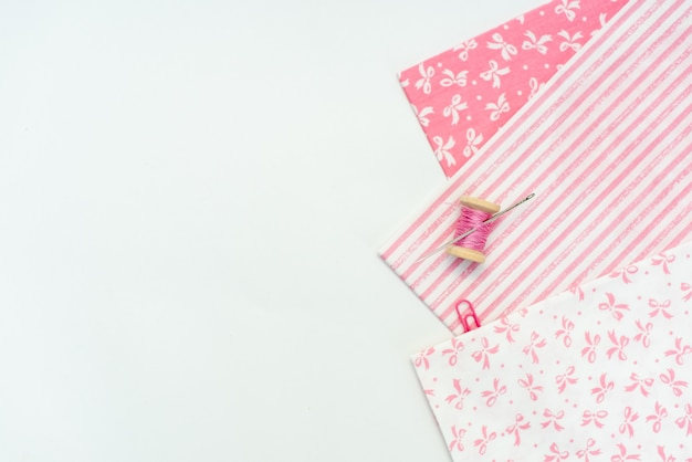 Tessuto naturale rosa e strumenti per cucire sul tavolo di legno bianco