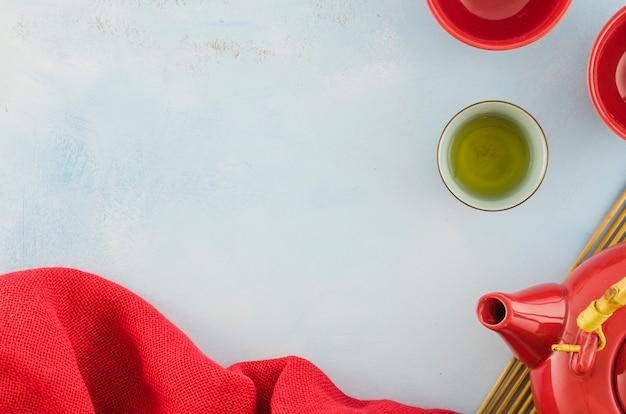 Tessuto rosso; tazze di tè e teiera con copyspace per scrivere il testo su sfondo bianco