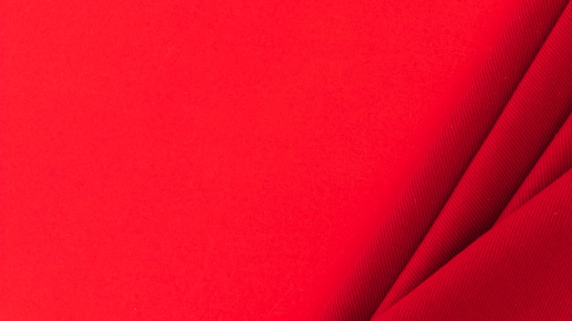 Tessuto tessile rosso piegato su sfondo colorato