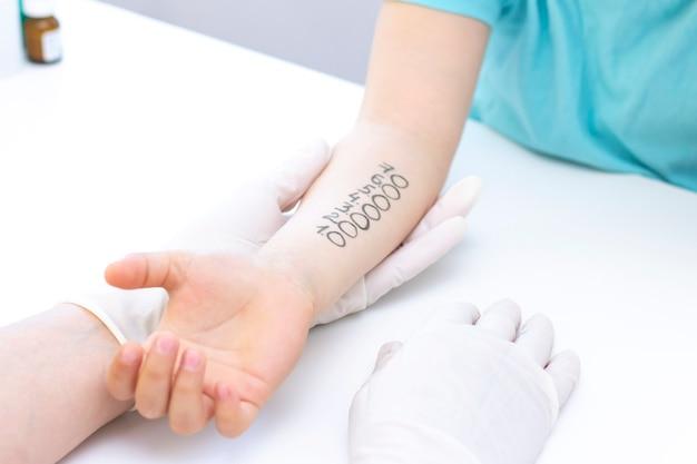 Test allergeni a portata di mano. bambino sottoposto a procedura di test cutaneo allergenico in clinica.