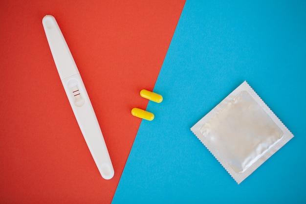 Test di gravidanza. il risultato è positivo con due strisce e preservativo con contraccettivo, pillola anticoncezionale, sesso sicuro, concetto sanitario