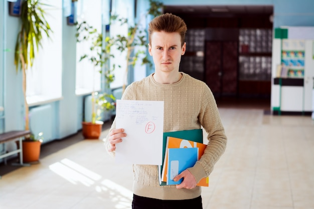 Test o esame fallito e studente arrabbiato nel corridoio dell'università con materiale didattico