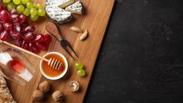 Testa del formaggio, mazzo di uva, miele, noci e bicchiere di vino sul bordo di legno e fondo nero con copyspace