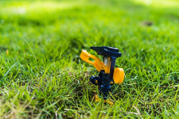 Testa dell'irrigatore che innaffia la macchia e l'erba verde nel giardino